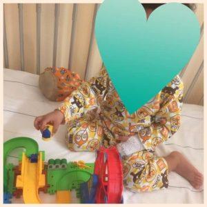 ベッドの上でおもちゃで遊んでいる息子の写真