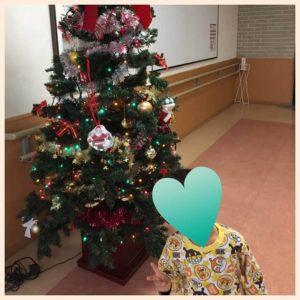 病院内クリスマスツリーの前でピースしている息子の写真